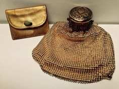 1930s vintage Whiting and Davis gold tone bubble mesh beggar bag purse. It is in great condition with minimal wear. It has a high quality gold colored grosgrain lining with the Whiting and Davis label. The expanding accordion gate at the top of the bag works very well and only has a few small spots of tarnish. The top or lid that comes down over the gate to close it, has a beautiful detailed design with a heart in the center and lots of intricate floral embellishments around the rim.