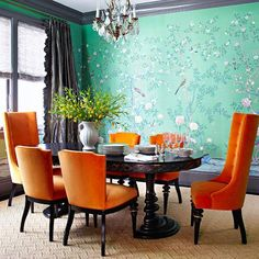 Formal dining rooms can occasionally come off as stiff and cold, but bold color is a cheer-giving anecdote. In this dining room, emerald green silk wallpaper wraps the space with easy-on-the-eyes color. Tangerine-color velvet chairs are unexpected yet make a statement. The high-gloss gray moldings and gunmetal taffeta panels grounds the room in sophistication.