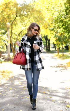 Black and white plaid coat, black sweater, skinny jeans, black ankle boots and a red handbag.