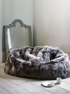 Carefully hand finished in the UK exclusively for Cox & Cox, our extra-large double beanbag has been made from 100% natural long-haired sheepskin in a stunning shade of mink. The perfect size for up to two people, each sumptuous double beanbag includes a non-slip grey leather base and is generously filled with beans. Suitable for the whole family, our large beanbag comfortable seats two adults and is ideal for relaxing and unwinding in. Also available in cool ivory, once you sink into our…