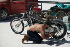 A Speed Week racer works on his bike ahead of a race. (Pic: ABC/Ginny Stein)