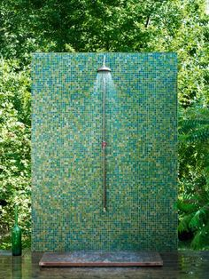 Outside shower in Sweden looks like garden art, copper shower fitting & base with Bisazzas L-Elba tiles in mosaic patter reflecting the greenery