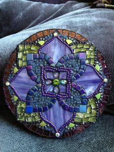 Magnifique mandala avec violets, des bleus et des verts, a un effet très apaisant. Jai utilisé un vitrail panaché et un verre vert très intéressant qui est gravé sur le dos. A aussi des cristaux avec un plus grand cristal vert, miroir et millefiori, perles au centre. One-of-a-kind, mesures de 6 pouces et est prête à suspendre.