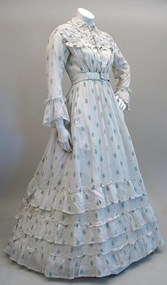 Victorian 1860s Civil War Cotton Print Dress in white and aqua. This lovely gown is a one-piece dress with an inset waistband, gathered skirt, and 3 tiers of flounces on the skirt. The bodice yoke is drawn up on tiny cords, the collar has a lace edging, the small white buttons are thread work over wood forms. The interior cotton bodice close with brass hooks and has hand done broderie anglaise  on the wide straps.