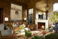 Designer John Oetgen used classic furniture, art, and quirky pieces (like the frog stool) to add personality to the oak-paneled living room in his North Carolina mountain house.      - Veranda.com