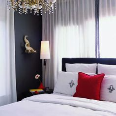 The Ikea light fixture next to the bed is customized with a tassel. Monogrammed pillows add yet another personal touch.