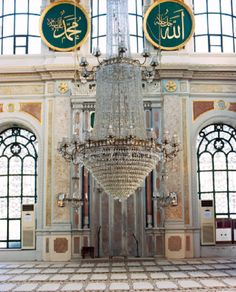 One of the large crystal chandeliers inside the Ortakoy Mosque in Istanbul, Turkey. The interior is elegantly decorated with Arabic words on the walls.
