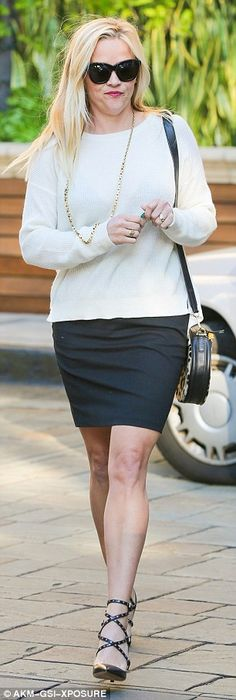 Always chic: Reese traded her red coat for a clingy black skirt and ivory jumper for the A...