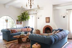 Covered in sumptuous blue velvet, these 8-foot-long chesterfield sofas are just as comfy as they are swanky. The drift-wood coffee table, layered rugs, old-world oil paintings, and pinky-red pillows warm up the blue-and-white scheme in this California bungalow.   - CountryLiving.com