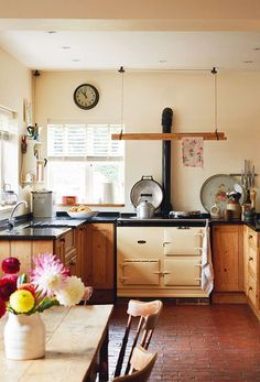 These homeowners love the original red-brick floor in their kitchen and had the existing Aga reconditioned, while the walls are painted in Farrow & Ball's Joa's White