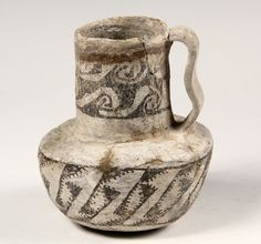 "SMALL ANASAZI POTTERY PITCHER - Cylindrical Form Pitcher with stepped in tall neck, sinuous strap handle, geometric decoration, 6 3/4"" tall."