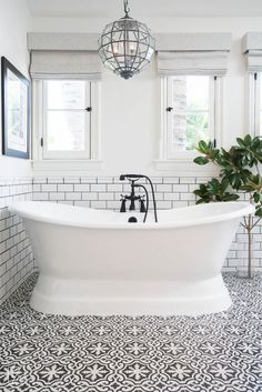 Stand alone bath tub with subway tiled walls and black and white patterned tile flooring | Lifestyle