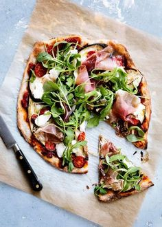 Pizza with ham, tomatoes, salad and artichoke