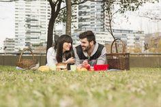 Gorrión delante de la joven pareja disfrutando en el picnic en el parque Foto gratis