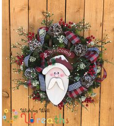 This Evergreen Santa wreath sports an adorable faced santa sled the sled gives this wreath a country christmas type feel. This Santa Wreath is covered in beautiful ribbons of red black and white. The Christmas wreath has an elegant yet fun look with the wooden snow covered ornaments, red berries, and peppermint candies that surround the fun faced santa sled. This wreath has a country farmhouse feel and would go well with any other Santa decor! This Santa wreath would look lovely on your…