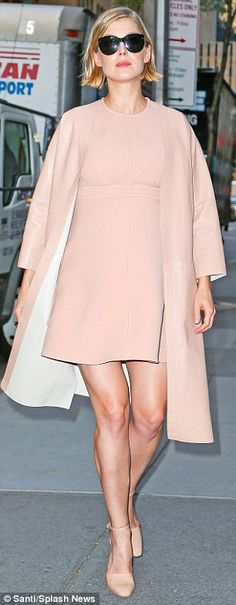 Rosamund Pike in a nude shift dress and coat.