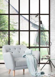 Baignée de lumière grâce à une verrière atelier, cette ambiance met en valeur un fauteuil pastel un brin rétro