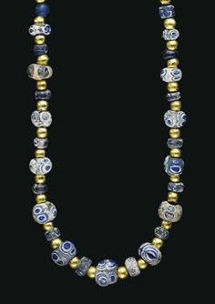 A MEDITERRANEAN GLASS EYE BEAD NECKLACE  CIRCA 6TH-2ND CENTURY B.C.  Composed of thirteen globular beads, turquoise in color, with stratified eyes layered in blue and white, interspersed with small blue glass beads, cylindrical striped glass beads, and modern gold spheres; strung with a modern hook-and-eye closure