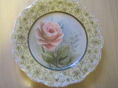 punainen ruusu. Reunoihin tehty kullanalusaineella kuviot, jonka jälkeen poltettu. polton jälkeen maalattu reunat irislysterillä.