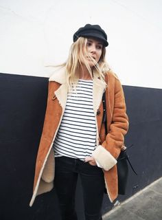 A striped shirt is worn with a suede shearling-lined coat, fisherman's cap, bucket bag, and skinny jeans