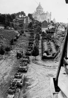 A column of British Cromwell and Sherman Firefly tanks of 1st RTR, 7th Armoured Division, enters Lisieux, 23 or 24 August 1944. In the background is the Basilica of St. Therese.