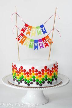 "Rainbow cake with ""HAPPY BIRTHDAY"" streamers"