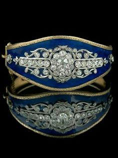 Victorian hinged cuff bracelet with a blue enamel background, set with a central oval European-cut center stone, surrounded by round European-cut and single-cut diamonds, the diamonds set in platinum and with an approximate total diamond weight of 3.61 carats.