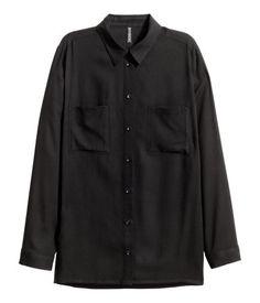 Schwarz. Gerade geschnittene Stoffbluse mit schmalem Turn-down-Kragen und zwei Brusttaschen. Die Bluse hat lange Ärmel mit schmaler Manschette.