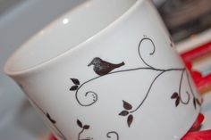 When we were having a huge family gathering I used a SHARPIE to write the names on the mugs (like you do on plastic cups, but this was to be a classier meal)  The Sharpie washed off in dishwasher without any problems!!  However, if you want it to stay, like this cute design, then use a PORCELAIN MARKER.