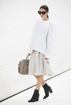 Zina Charkoplia of FashionVibe wears a white sweatshirt, knee-length skirt, black ankle boots, a gray satchel bag, and cat-eye sunglasses
