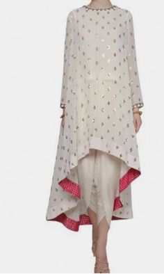 Vvani by Vani Vats Featuring an off white asymmetrical kurta in georgette base embellished with sequin hand embroidery and brocade inline borders. It is paired with dhoti pants in crepe base.Costumised similar dress for order HOUSE OF ZUHAF Pakistani Dress Design, Pakistani Outfits, Indian Outfits, Indian Designer Outfits, Designer Dresses, Designer Clothing, Designer Kurtis, Kleidung Design, Desi Clothes