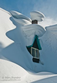 Lots of snow on the roof of this building at Roger's Pass. Roger's Pass in the Selkirk Mountains of BC is famous for the quantities of snowfall. This building is closed in winter for obvious reasons. This window is on the second floor showing here that the ground floor is completely buried.