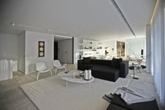 Black Sofa And Cushions Combined With White Chairs And Oval Table On White Carpet