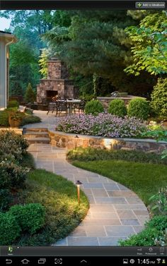 Love the stone wall raising the garden and the outdoor fireplace.