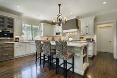 Large white kitchen with custom white cabinets and elevated white island with seating for three people