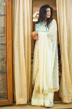 Rain clouds are on their way and hope is in the air! A lovely feminine drape in a super soft french lacy net. Pristinely pure and ever so classy…Pair with a pastel blouse to float on those clouds. Or strike out in a contrast blouse to stand out. Any which way you pair this beauty, this saree makes a perfect blank canvas! #frenchnet #lace #cream #saree #India #blouse #houseofblouse