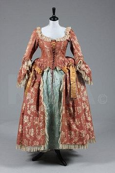 A brocaded silk open robe and petticoat, 1760s of dark cinnamon silk brocaded with trails of ivory blooms, with original braid trimmed engageants, 1880s added gold satin trimming; with a quilted pale blue silk petticoat