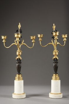 A pair of Empire bronze and marble candelabras with three lights supported by bronze caryatids with dark brown patination, dressed in long tunics à lantique and leaned at a... 5,200€