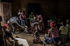 Residents gather inside a makeshift sewing studio in the village of Mangango, in the eastern Democratic Republic of Congo, 2014 - by Pete Muller (1982), USA