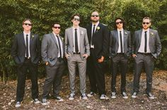 Love the mixture of grey and black suits with black sneakers. And of course with the sunglasses.