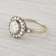 Diamond Edwardian Cluster Ring (Made in PLATINUM on gold and centered with a old european cut diamond. Center diamond is accented by single cut diamonds and elegant MILLEGRAIN edges in a motif of a flower. A truly charming ring with a delicate thin band. Perfect for lovers of bygone times. Circa 1900)