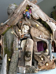 Garden fairy home made from driftwood and other trinkets. Love the lion's head door knocker!