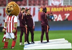 Barcelona's French defender Samuel Umtiti (R) and Barcelona's French defender Lucas Digne (C) stand on the pitch next to the Olympiakos mascot, prior to the UEFA Champions League group D football match between FC Barcelona and Olympiakos FC at the Karaiskakis stadium in Piraeus near Athens on October 31, 2017.  / AFP PHOTO / ARIS MESSINIS - 4 of 90