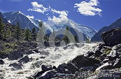 Mountain stream with breakneck speed rushing into the valley, paving its course between huge boulders