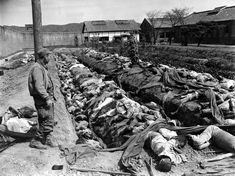 Bodies of some 400 Korean civilians lie in and around trenches in Taejon's prison yard during the Korean War, on September 28, 1950. The victims were bound and slain by retreating Communist forces before the 24th U.S. Division troops recaptured the city September 28. Witnesses said that the prisoners were forced to dig their own trench graves before the slaughter. Looking on, at left, is Gordon Gammack, war correspondent of the Des Moines Register and Tribune.