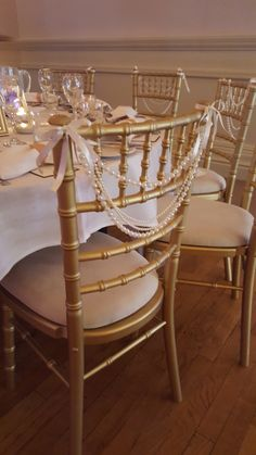 Maybe do something like this for head table??? Pearl garland on the backs of gold chivari chairs.