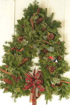 The natural look, with pine cones and assorted greens, is popular with wreaths. These wreaths shaped like Christmas trees can be found at Lockwood's Greenhouses in Hamburg, NY. Photo copyright Connie Oswald Stofko