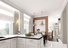 Aranżacja białej kuchni z ceglaną ścianą i chromowanymi loftowymi lampami nad stołem w jadalni. Blat wykonany jest z białego konglomeratu z wzorem kamiennym i wykończony drewnianym profilem od spodu, aby dodać mu dekoracyjności.