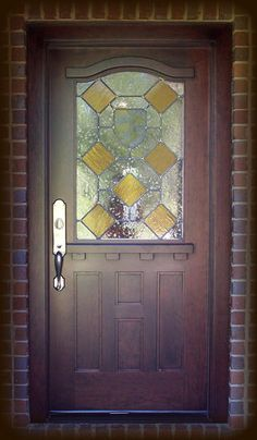 "DbyD-4014.  Here is a popular 36"" x 80"" Honduran Mahogany door is installed in a home in Auburn, Alabama.  It is shown with custom leaded seedy glass with amber diamonds and a hand painted and fired shield in the center.  The heavy ledge and dentil is reminicent of designs by Frank Loyd Wright.  The hardware is Rocky Mountain hand cast bronze."