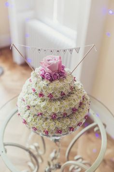 A wedding cake of flowers with mini bunting topper - Image by Claire Penn Photography - Jenny Packham wedding dress & Harriet Wilde shoes for a classic wedding with bright florals & Coast pastel bridesmaids dresses. Groom wears Marc Wallace suit.